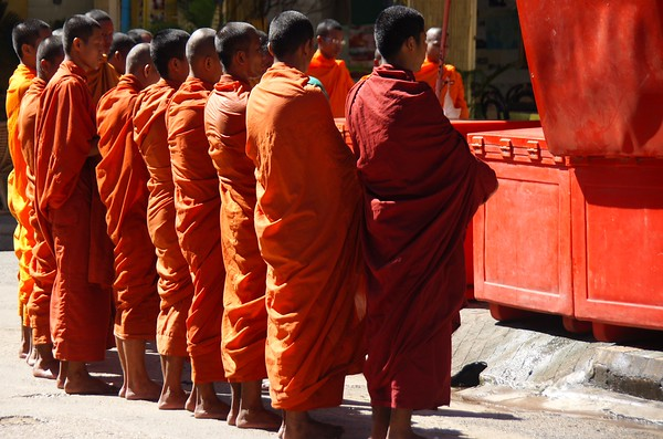 A group of monks stand still during their morning Alms Giving routine in Battambang, Cambodia.