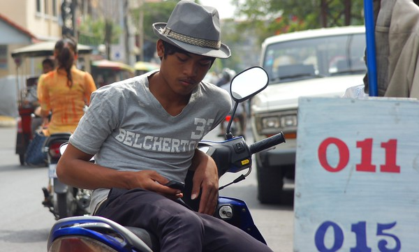 A Khmer man lounges on his motorbike text messaging during the mid-afternoon - Phnom Penh, Cambodia.