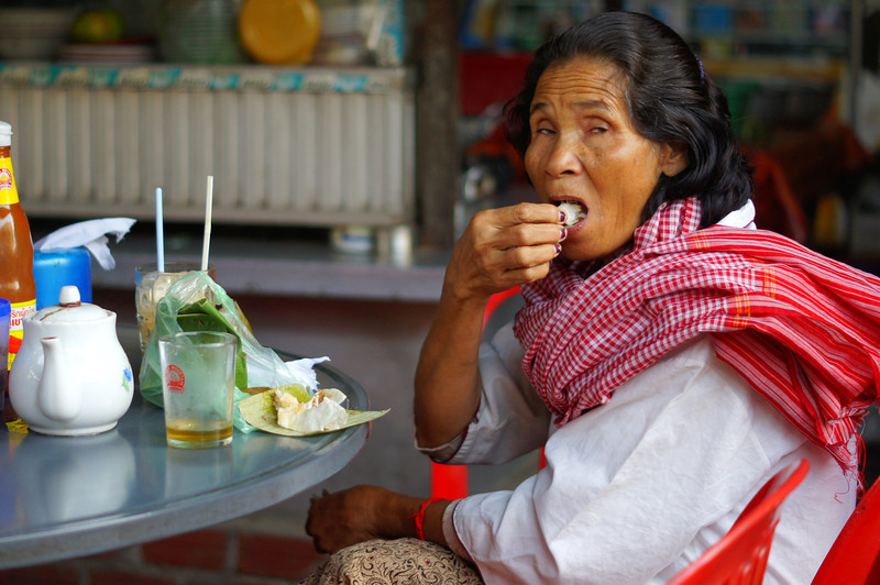 This Khmer lady sits down for tea and snack as she puts food into her mouth at the moment I snapped this picture - Battambang, Cambodia.