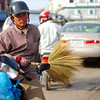This Khmer man is carrying a load up front and a broom on his motorbike braces - Battambang, Cambodia.