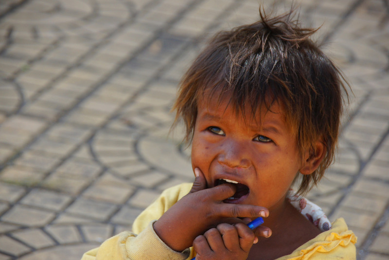 A street child points to her mouth to indicate she wants food - Phnom Penh, Cambodia.