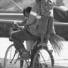 A Khmer man carrying a broom rides his bicycle with two children on board.  One girl in the front and a boy standing on the back looking behind and smiling while making a peace sign for the camera - Battambang, Cambodia.