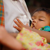 An infant feeds from her mother's breast at the Central Market (Psar Nath) - Battambang, Cambodia.
