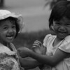 Two of the most adorable and cute girls I've ever seen are delighted by my presence and laugh and smile uncontrollably - Battambang, Cambodia.
