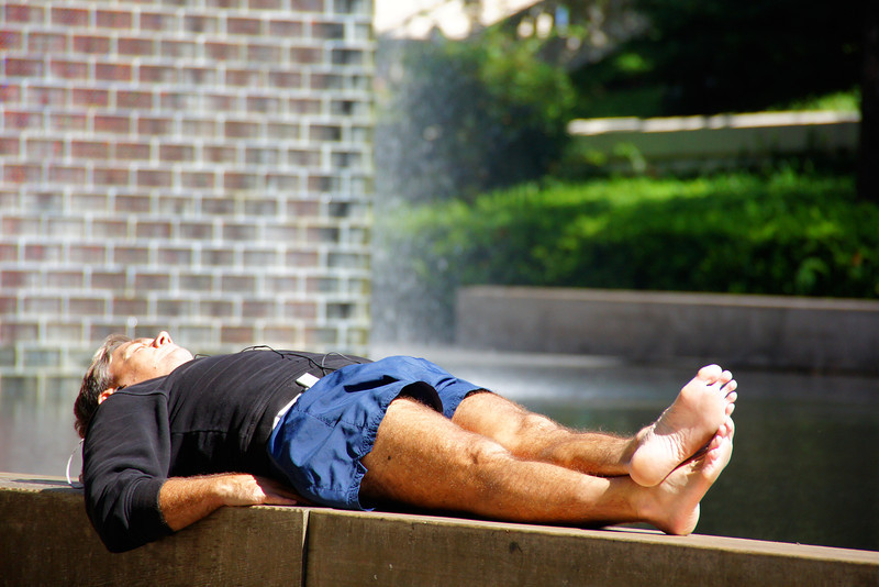 A man stretches out and enjoys listening to his MP3 player on a gorgeous afternoon at Millennium Park.
