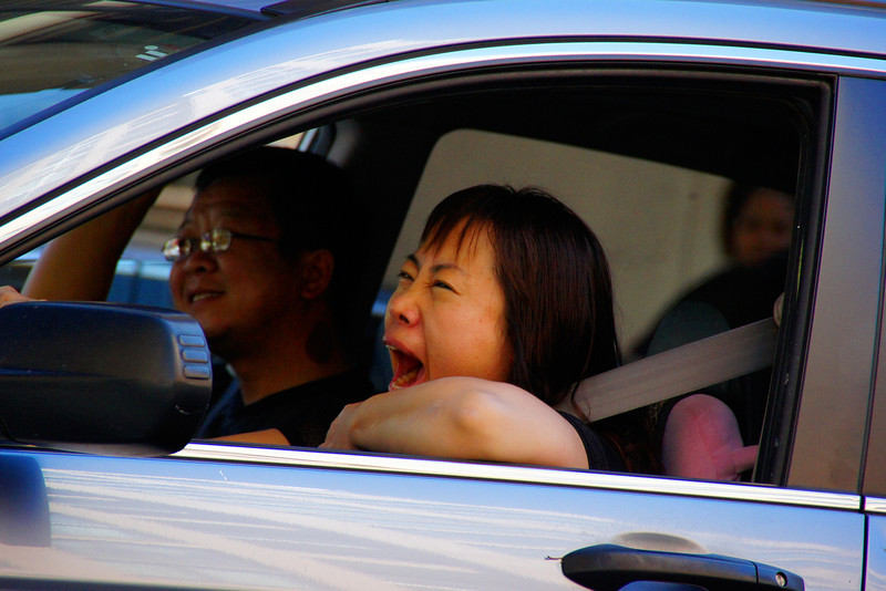 A lady yawns in her car during rush hour in the city.