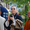 A monk wielding a dSLR contemplates taking a photo in Chinatown.