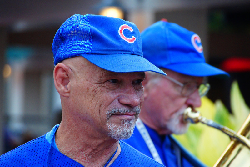 A band wearing Chicago Cubs uniforms performs music for fans waiting to get into Wrigley Field.