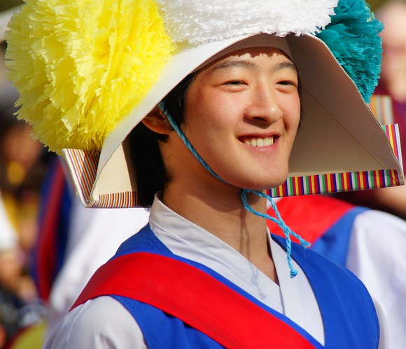 A smiling Korean performer delights the onlooking crowd with his spectacular acrobatics in a traditional performance at the Korean Folk Village in Yongin - South Korea.
