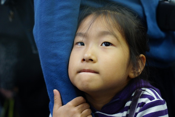 A cute Korean girl grasps ahold of her mother's arm at a subway station stop in Seoul, South Korea.
