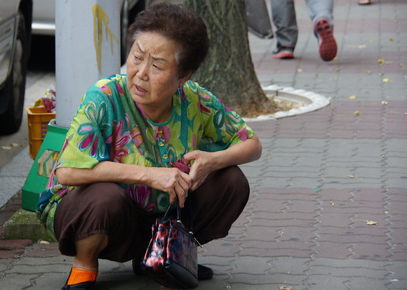 An elderly lady crouches down on quiet street located in Incheon, South Korea.