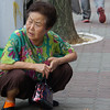 """<a href=""""http://nomadicsamuel.com"""">http://nomadicsamuel.com</a> : An elderly lady crouches down on quiet street located in Incheon, South Korea."""