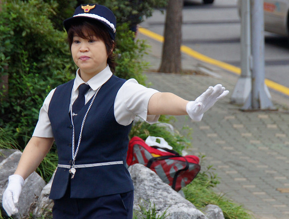 A Korean traffic attendant motions with her left arm for vehicles to stop in order for a group of students to cross this busy intersection located in Incheon, South Korea.
