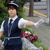 """<a href=""""http://nomadicsamuel.com"""">http://nomadicsamuel.com</a> : A Korean traffic attendant motions with her left arm for vehicles to stop in order for a group of students to cross this busy intersection located in Incheon, South Korea."""