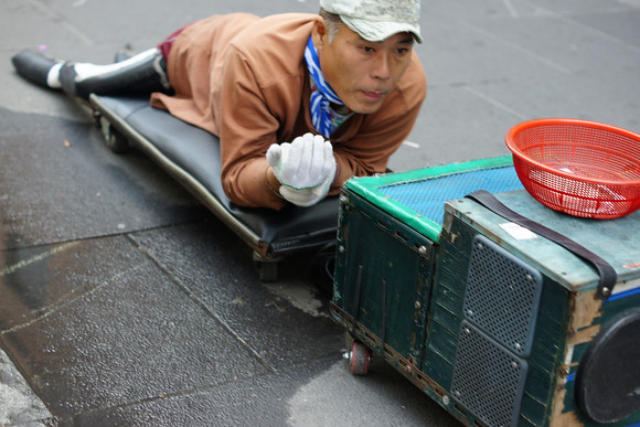 A Korean begger scrapes along the pavement wearing a special outfit that appears to be made out of rubber as he plays music from his system and collects donations in the red basket along Insadong Avenue located in Seoul, South Korea.