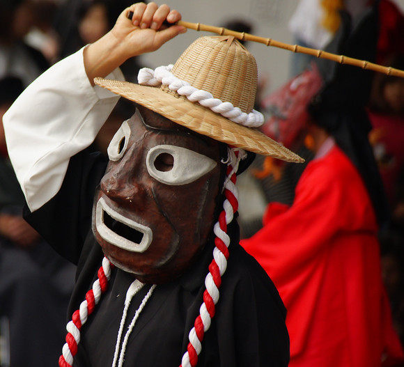 A traditional Korean performer wearing a folk mask performs slow, deliberate movements just outside of Gyeongbokgung Palace - Seoul, South Korea.