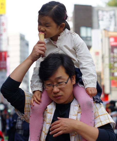 A girl enjoys a bite out of an ice cream cone offered by Dad as they wander along the hectic Insadong avenue located in Seoul, South Korea.