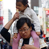 """<a href=""""http://nomadicsamuel.com"""">http://nomadicsamuel.com</a> : A girl enjoys a bite out of an ice cream cone offered by Dad as they wander along the hectic Insadong avenue located in Seoul, South Korea."""
