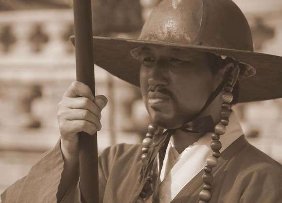 This Korean man stands tall and stoic as he prepares to conduct a changing of the Guard ceremony in front of a large audience at Gyeongbokgung Palace in Seoul, South Korea.