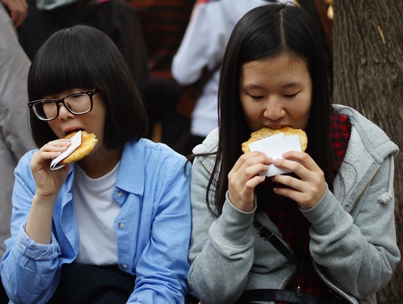 Two Korean students enjoy a street side snack along the bustling Insadong district area - one of the most popular tourist destinations in all of Seoul, South Korea.