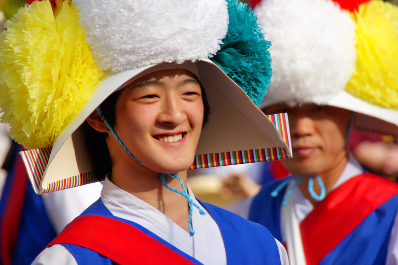 A young Korean man with wonderful smiling faces poses for the crowd after performing a traditional farmers dance.