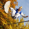 This energetic entertainer is performing spectacular jumps on a tightrope while doing a coordinated fan dance.