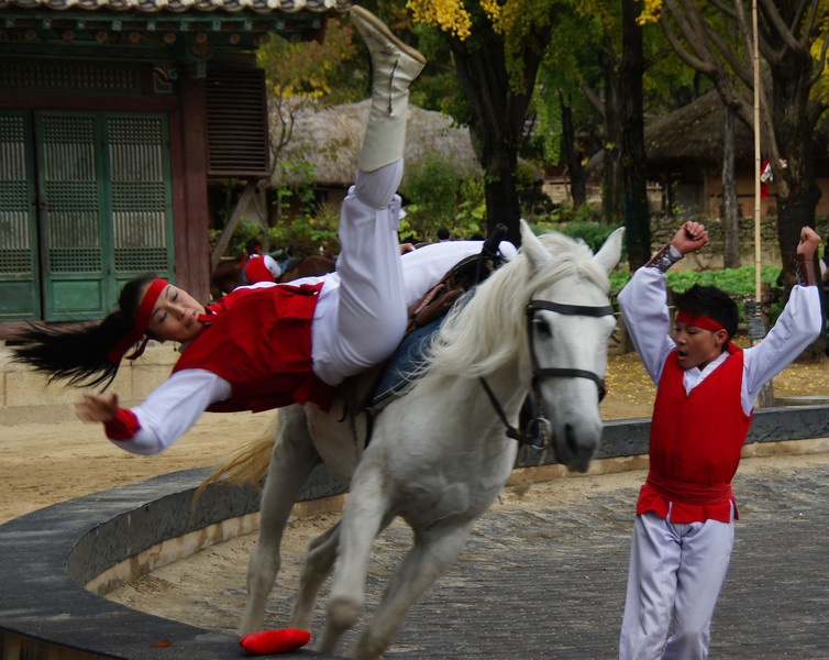 A Korean equestrian performer jolts her body downwards, in an attempt to pick up the red cloth, while a young Korean boy cheers her on.