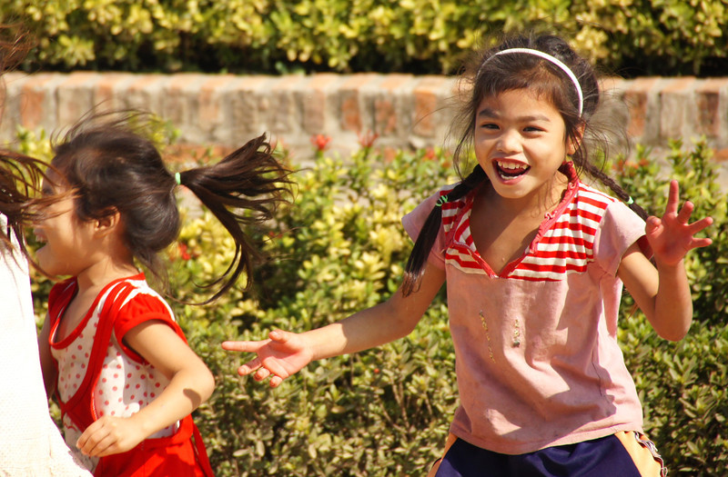 A candid moment where this girl is happily playing with her friends - Luang Prabang.