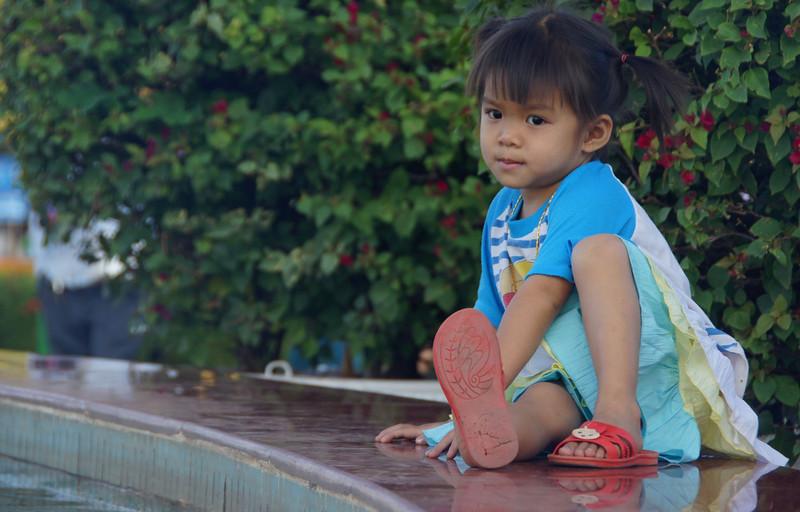 A charming little girl sits down near the fountain - Vientiane.