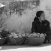 Two ladies with baskets of fruit wait for potential customers - Luang Prabang.