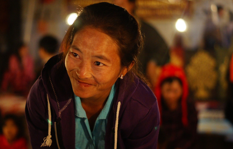A lady bends over and smiles at the local night market - Luang Prabang.