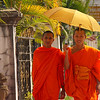 Two smiling monks walk down the side-walk with sun umbrellas - Luang Prabang.