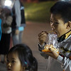 A boy enjoys a late night snack - Vientiane.