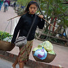 A young lady carries a yoke full of fresh produce - Luang Prabang.