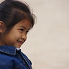 An adorable girl flashes a smile towards her mates on the playground - Luang Prabang.