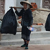 A lady collecting discarded soda bottles - Luang Prabang.