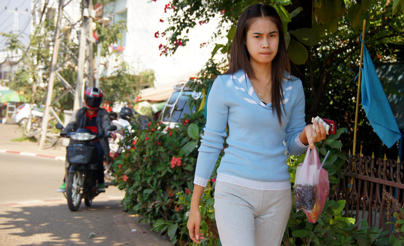 A lady carries some refreshing drinks filled with ice inside plastic bags - Vientiane.