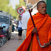 A monk walks down the street carrying an umbrella - Luang Prabang, Laos.