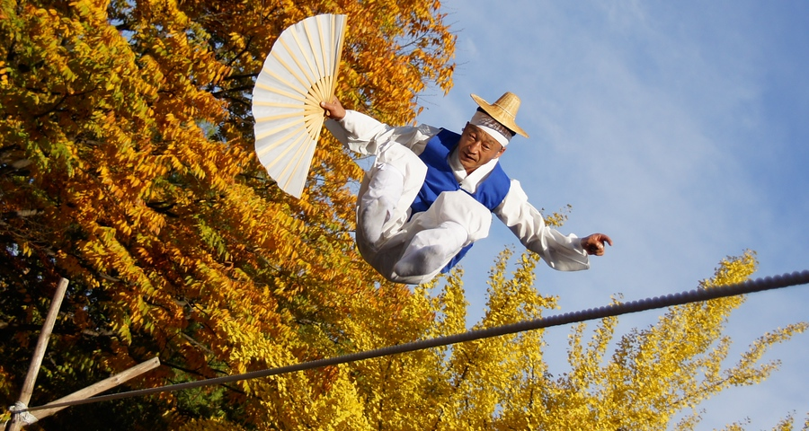 A Korean man performs an impressive stunt on a tightrope - Korean Folk Village: Yongin, South Korea.