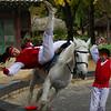 A Korean equestrian performer reaches for red ribbon as the boy cheers her on - Korea Folk Village: Yongin, South Korea.