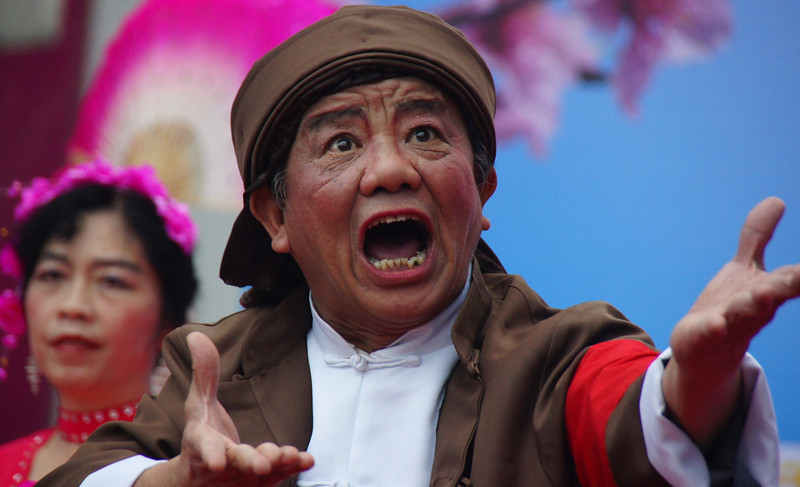 A passionate Chinese comrade performers for an audience on the street - Guilin, China.