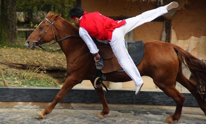 A Korean man leaps onto a galloping horse during an equestrian performance - Korean Folk Village: Yongin, South Korea.