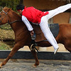 A Korean man leaps onto a galloping horse during an equestrian performance - Korean Folk Village: Yongin, South Korea.