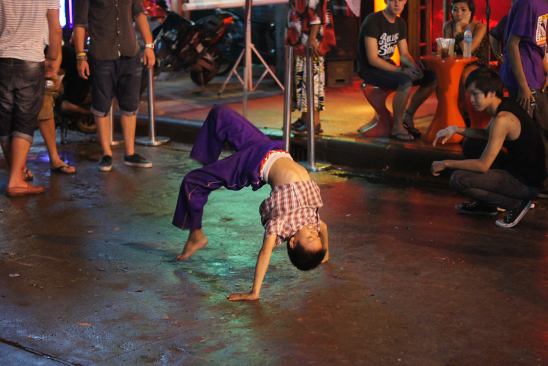 A Thai boy break-dances on the street for an audience of both foreigners and Thais - Khao San Road: Bangkok, Thailand.