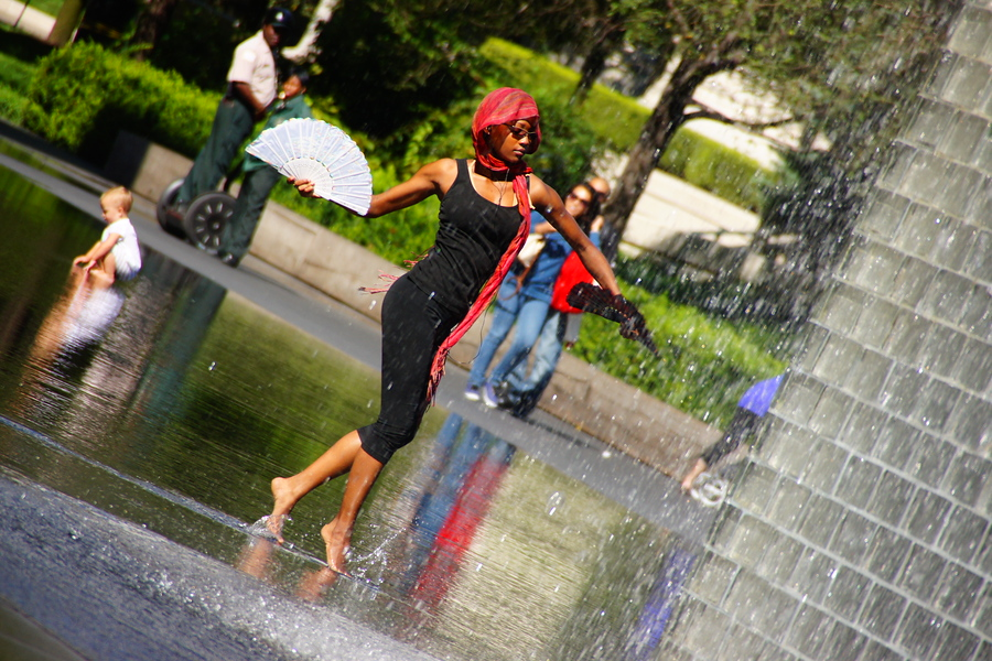 A lady elegantly manoeuvres across the public square and fountain area of Millennium Park - Chicago, Illinois.