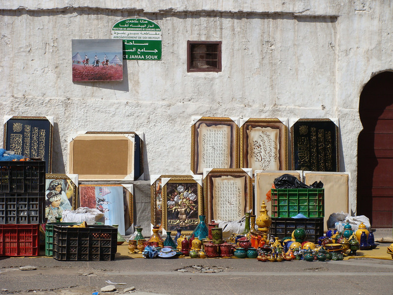 This is a picture of a street scene (crafts and artwork against a wall) in Casablanca, Morocco.