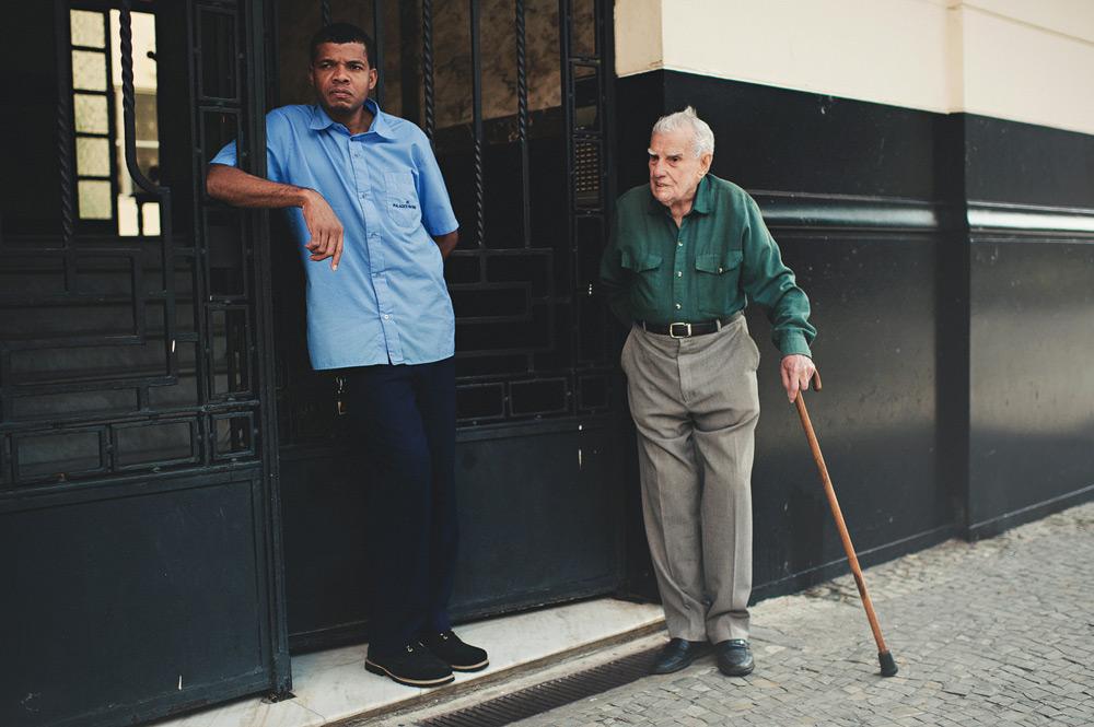 An elderly man and his caretaker relaxing outside in Rio de Janeiro, Brasil