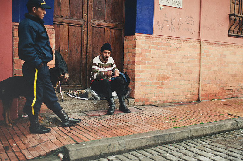 A police officer walks past a person living on the streets of Bogota, Colombia