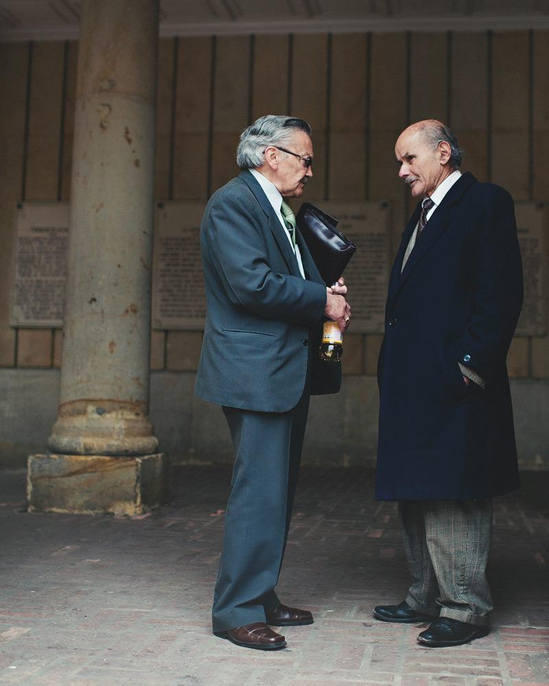Two gentlemen dressed in formal attire talking in Bogota, Colombia