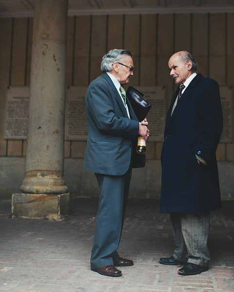 Two gentlemen dressed in formal attire talking in Bogota, Colombia